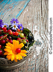 half of the plate with the leaves and berries of black and red currant with a flower on a wooden background