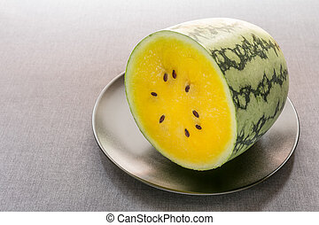 Half of yellow watermelon on black plate with gray tablecloth background.