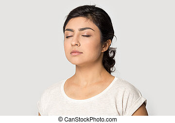 Half side view peaceful millennial indian girl meditating...