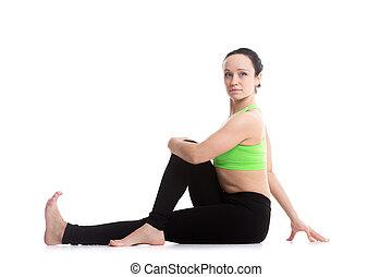 Half Spinal Twist yoga pose - Beautiful athletic woman...