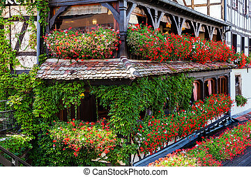 half timbered house with balconies full of flowers in Strasbourg, France