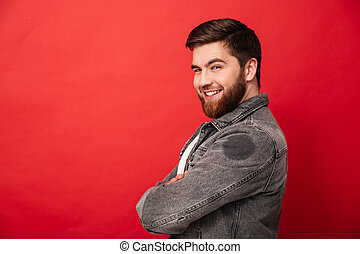 Half turn portrait of attractive man in jeans jacket posing on camera with amazing smile and arms folded, isolated over red background