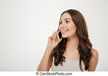 Half-turn portrait of caucasian woman with long brown hair smiling while having pleasant mobile conversation on her smartphone, over white wall