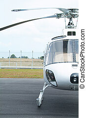 Front view of small, white helicopter at an airport. Only half of helicopter shown.