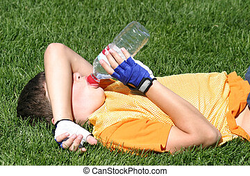 This boy was resting at halftime of a soccer game. Hie was tired and laying down on his back while taking a long drink of water during the timeout break.