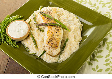Halibut with asparagus risotto on green plate