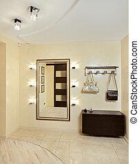 Hall in beige tones with hallstand and golden mirror