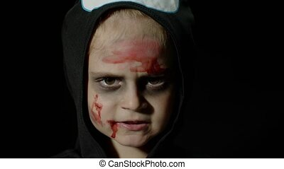 Halloween, angry girl with blood makeup on face. Kid dressed as scary skeleton, posing, making faces