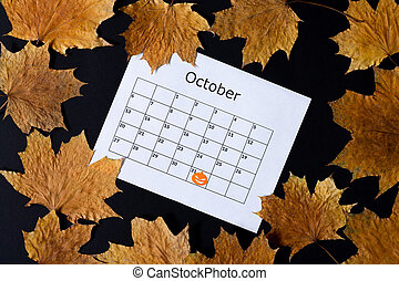 Halloween background. Calendar page with mark on October 31 and fall on dark table top view