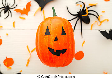 Halloween background with jack-o'-lanter, paper bats, spiders, confetti on white wooden background. Halloween holiday decorations. Flat lay, top view. Party invitation mockup, celebration.