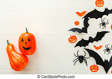 Halloween background with jack-o'-lanter, pumpkins, paper bats, spiders, confetti on white wooden background. Halloween holiday decorations. Flat lay, top view. Party invitation mockup, celebration.
