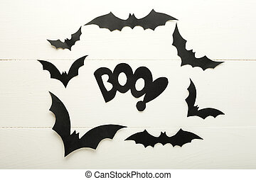 Halloween background with paper bats and BOO lettering on white wooden background. Halloween holiday decorations. Flat lay, top view, copy space. Party invitation mockup, celebration.