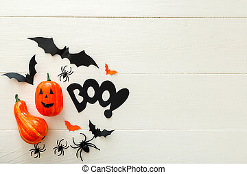 Halloween background with paper bats, spiders, jack-o'-lantern on white wooden background. Halloween holiday decorations. Flat lay, top view, copy space. Party invitation mockup, celebration.