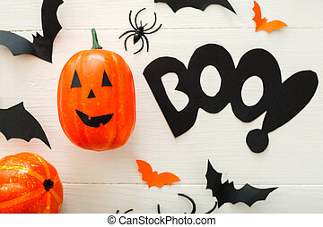 Halloween background with paper bats, spiders, jack-o'-lantern on white wooden background. Halloween holiday decorations. Flat lay, top view. Party invitation mockup, celebration.