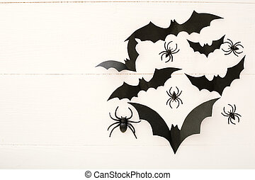 Halloween background with paper bats, spiders on white wooden background. Halloween holiday decorations. Flat lay, top view, copy space. Party invitation mockup, celebration.