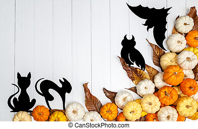 Halloween background with pumpkins, black cats, a black owl and a black paper bats on white backdrop. Copy space for text. Festive concept. Top view.
