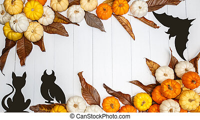 Halloween background with pumpkins, black cats and a black paper bats on white backdrop. Copy space for text. Festive concept. Top view.