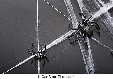 Halloween background with spiders and spider web on black background. Halloween holiday decorations. Flat lay, top view, copy space.