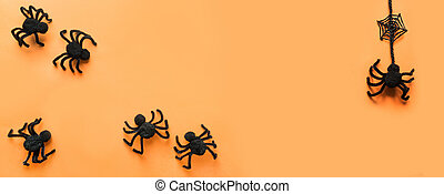 Halloween banner with black spiders, web on orange. Flat lay, top view. Space for text.
