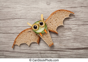 Halloween bat made of bread on wooden background