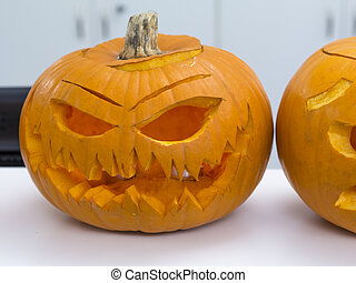 Halloween big orange pumpkin decorated with scary face. Jack O' Lantern on white table background