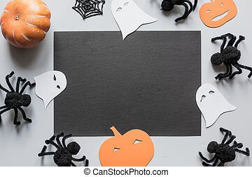 Halloween blank with space for text and party decor, black spiders, pumpkin, on grey. Flat lay, top view, copy space.