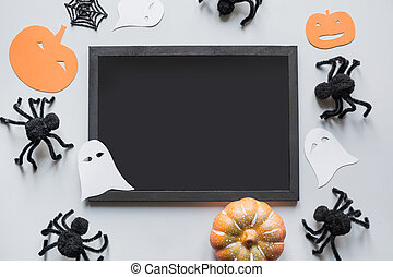 Halloween blank with space for text and party decor, black spiders, pumpkin, white ghost on grey. Flat lay, top view, copy space.