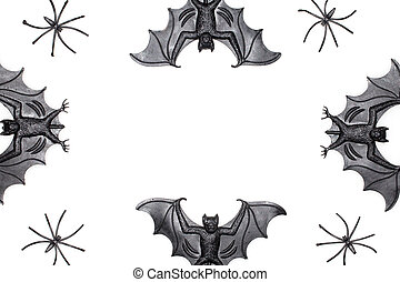 Halloween border image with novelty spooky bat and spider toys on white background