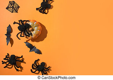 Halloween border with black spiders on orange background. Flat lay, top view, copy space.
