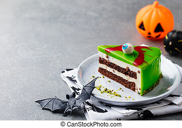 Halloween cake on a white plate with holiday table decoration. Grey background. Copy space.