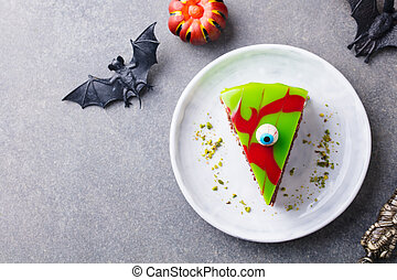 Halloween cake on a white plate with holiday table decoration. Grey background. Copy space. Top view.