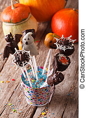 Halloween cake pop on the table and pumpkins. vertical