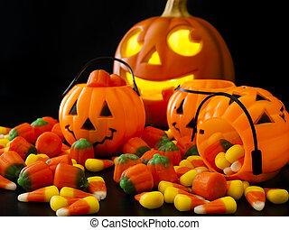 Halloween candies spilled on black background.