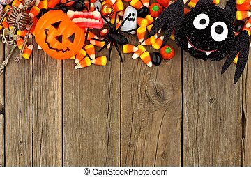 Halloween candy and decor top border against wood -...