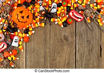 Halloween candy and decor top corner border against rustic wood