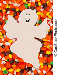 Halloween candy corn background with spooky ghost for your message