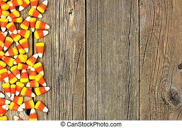 Halloween candy corn side border against wood