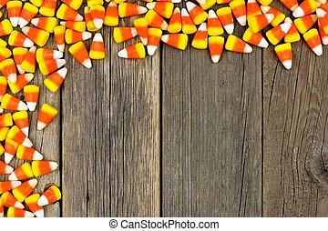 Halloween candy corn top corner border against wood