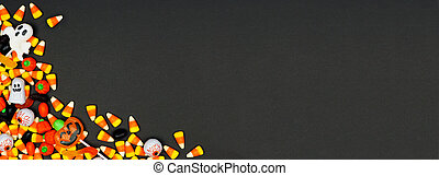 Halloween candy corner border banner. Top view on a black background with copy space.