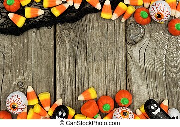 Halloween candy double border against a rustic wood background