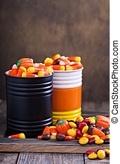 Halloween candy in small tins on brown rustic table