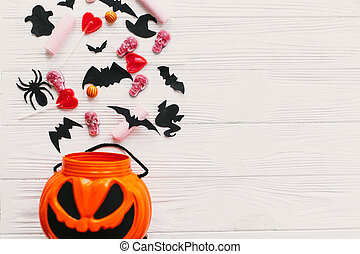 Halloween candy spilled from jack o lantern bucket with skulls, black bats, ghost, spider decorations on white wooden background, flat lay. Halloween sweets. Copy space. Trick or treat
