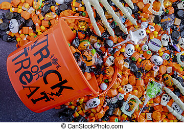 Halloween candy spilling out of orange trick or treat bucket...