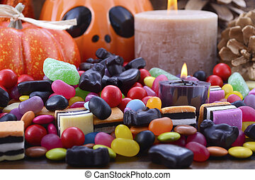 Halloween Candy with pumpkins on dark wood background.