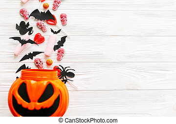 Halloween candy with skulls, black bats, ghost, spider decorations spilled from jack o lantern bucket on white wooden background, flat lay. Halloween sweets. Copy space. Trick or treat