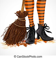 Halloween closeup witch legs in boots and with broomstick standing on fallen leaves isolated on a white background