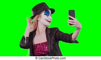 halloween clown make-up taking a selfie mobile phone -...