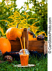 Halloween cocktail with pumpkins decoration on background. Punch for a party. Jack-o-Lantern.