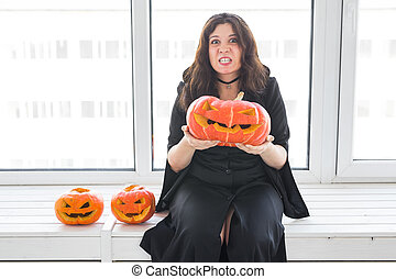 Halloween concept - Angry witch with pumpkin Jack-o'-lantern on light background