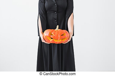 Halloween concept - Anonymous witch with pumpkin Jack-o'-lantern on light background
